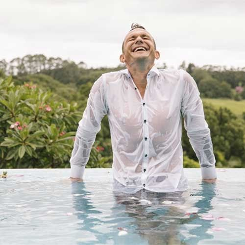 Man who has just falllen in the pool during his photshoot, he is laughing and soaking wet