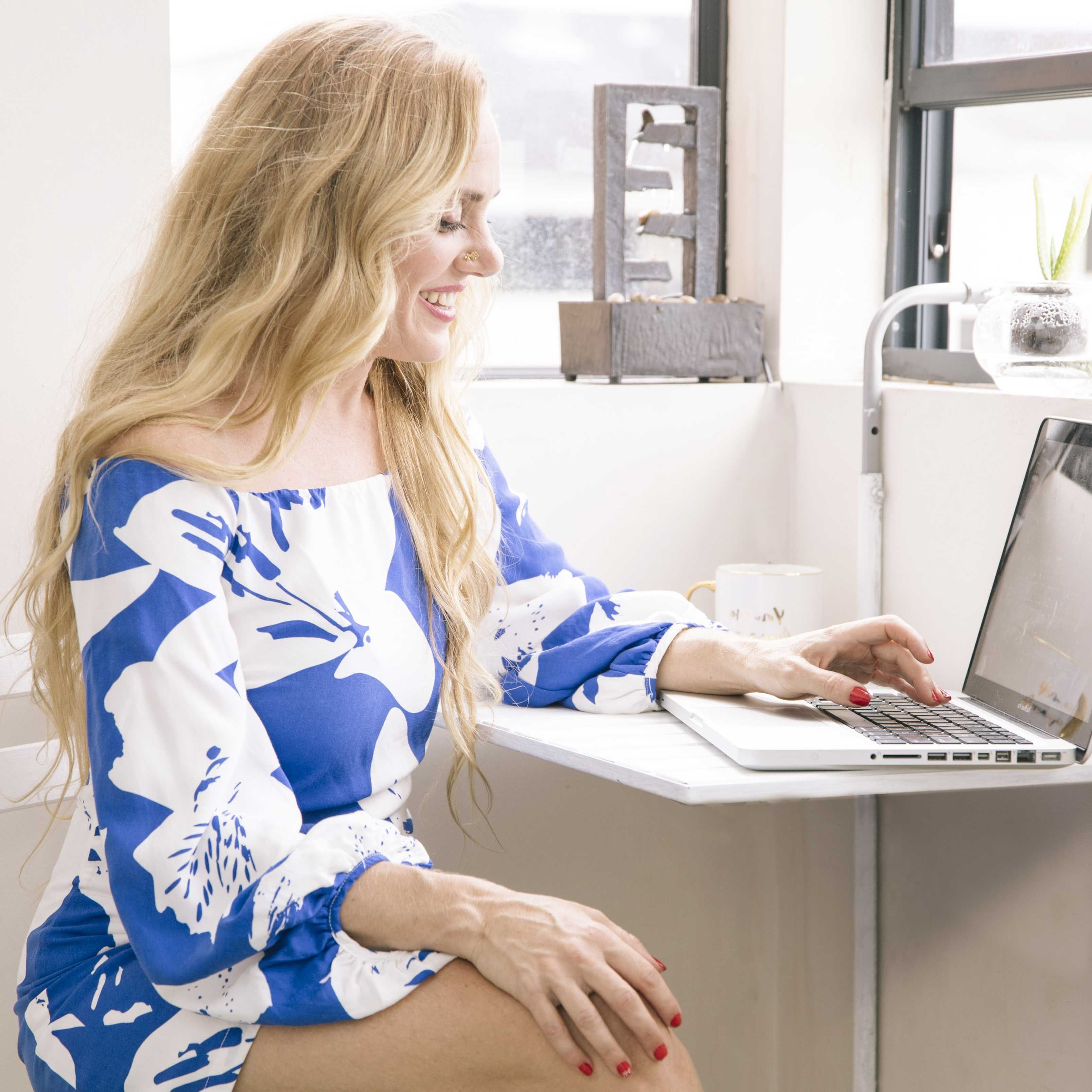 Business woman laughing in her branding photoshoot while using a laptop in a coffee shop