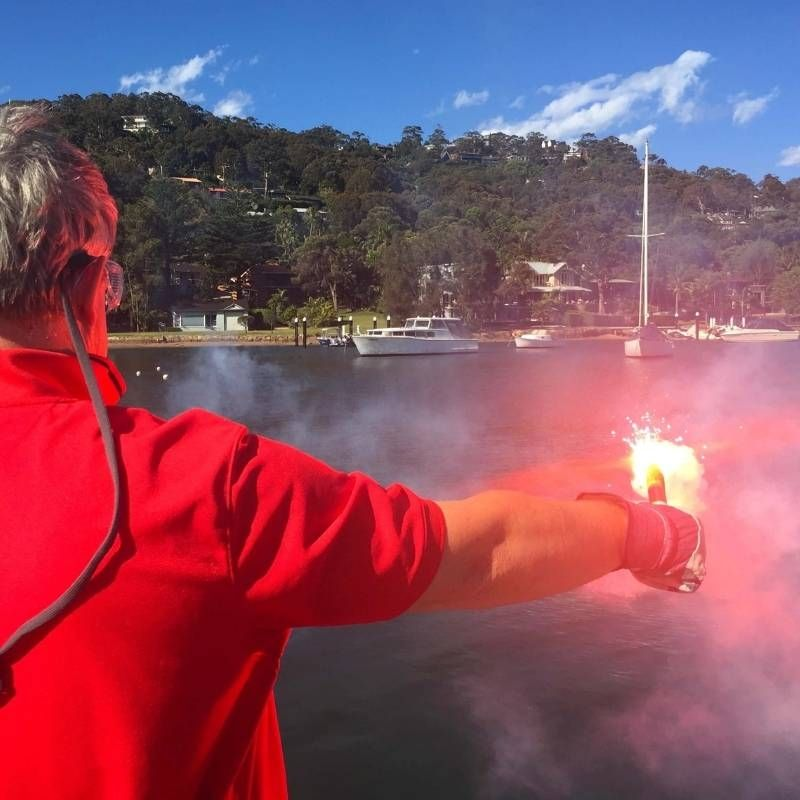 Man in a red shirt setting off a red handheld day flare on a sea survival course at the royal prince alfred yacht club