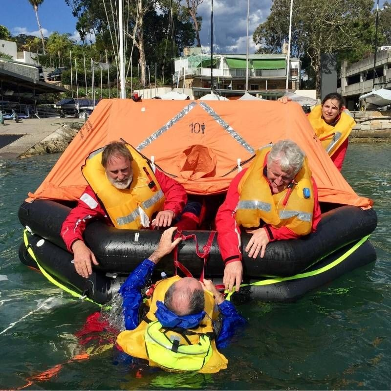 People doing a sea safety and survival course getting into an orange and black liferaft at the royal prince alfred yacht club.